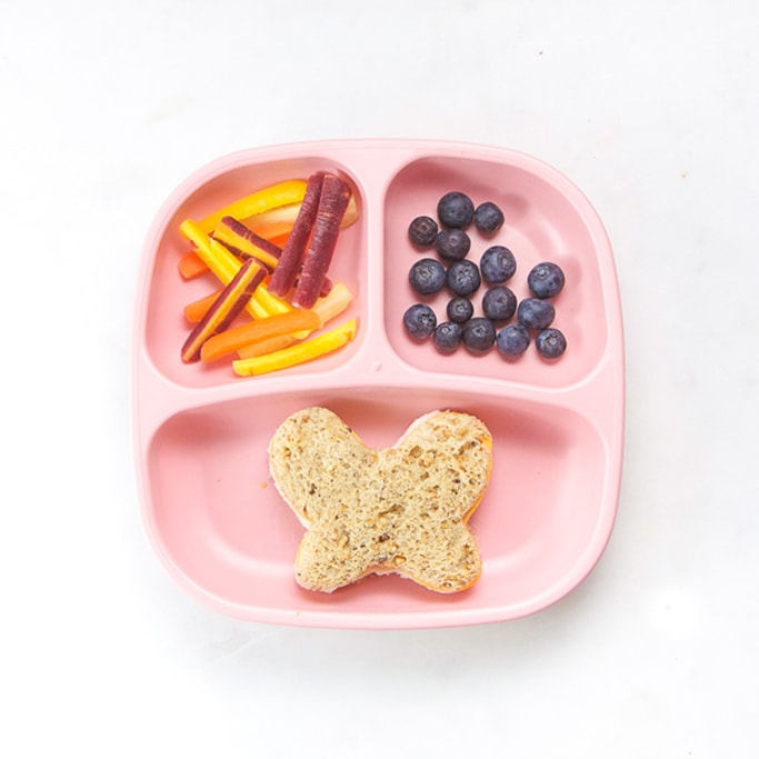 3-section plate on a white surface filled with toddlers lunch - butterfly cut out sandwich, blueberries and cut tri-colored carrots.
