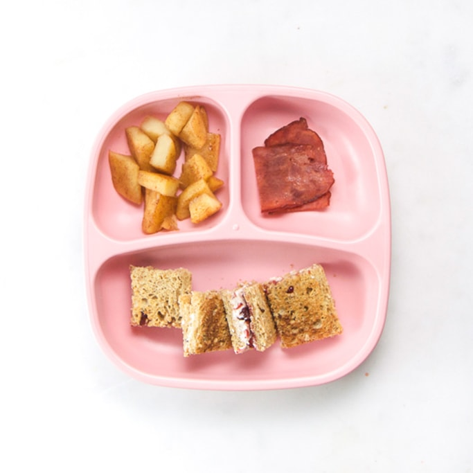 3-section plate on a white surface filled with a healthy toddler meals - cream cheese sandwiches, stewed apples and turkey bacon.