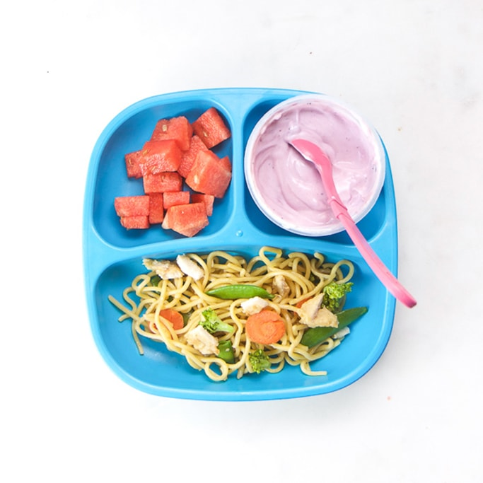 3-section plate on a white surface filled with toddlers lunch - leftover chicken noodles, watermelon and yogurt.