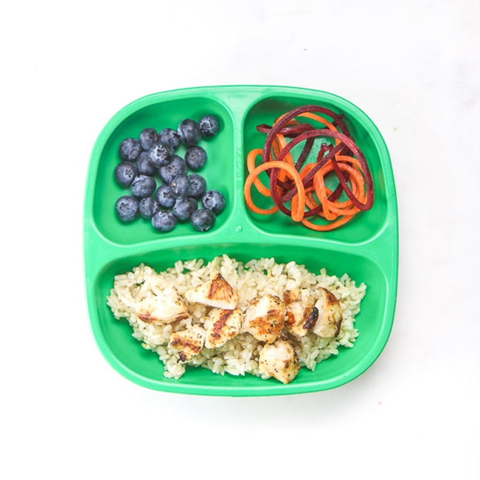 3-section plate on a white surface filled with healthy toddler meals - chicken, rice, blueberries and beets and carrots.