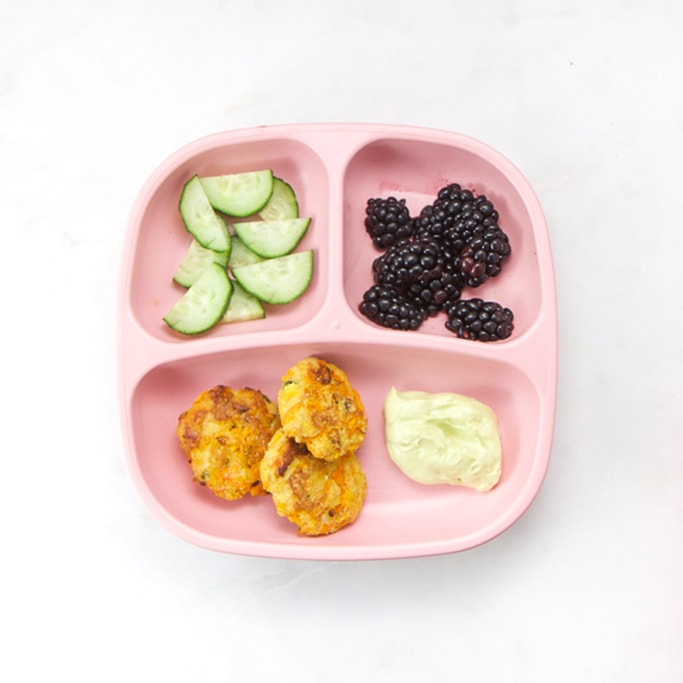 3-section plate on a white surface filled with healthy toddler meals - turkey and sweet potato poppers, blackberries and cucumbers.