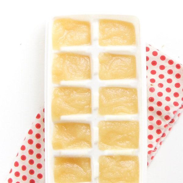 A white ice cube freezer tray filled with a homemade baby food puree.