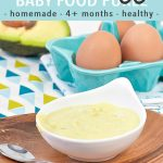 graphic for post- text reads avocado egg baby food puree - homemade - 4+ months - healthy. Image is of a small white bowl filled with a creamy egg and avocado puree. The bowl is sitting on a wooden plate and there are eggs and avocado behind the bowl.