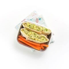 a white bento box is filled with a mini pita pocket cut in half and filled with an avocado tuna salad, there are cut sticks of carrots on the plate as well. The plate is sitting on a multi-colored napkin on a white surface.