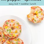 """graphic for post - text reads bagel pizzas with pepper """"sprinkles"""" easy kid+toddler lunch. Image is of a round white plate sitting on a white surface. On the plate are 3 mini bagel pizzas and there is one bagel pizza sitting on the surface with a bite taken out."""