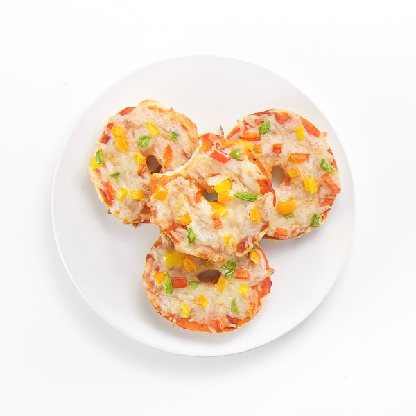 round white plate sitting on white surface. On the plate there are 4 mini bagel pizzas stacked on top of each other. The top bagel pizza has a bite taken out it.