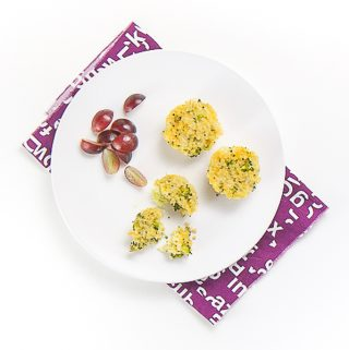white plate sitting on top of a purple napkin on a white surface. On the plate is 3 mini cheesy broccoli quinoa bites and a small handful of sliced grapes. One of the quinoa bites is halfway eaten with a fork.