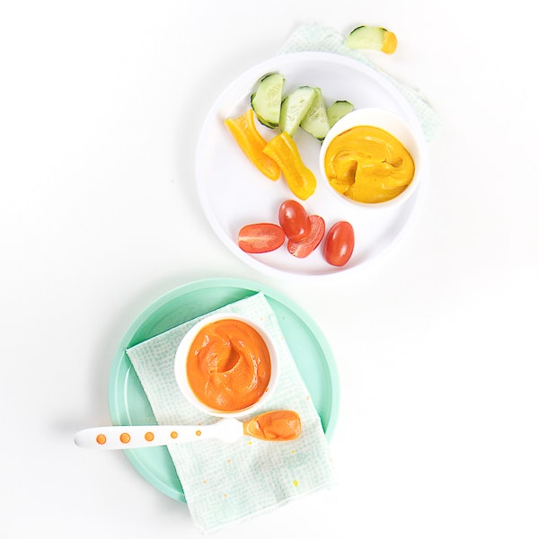 2 plates - one white and one teal - sitting on a white surface. Teal plate has a small white bowl with a bright baby food puree in it. The white plate has a white bowl filled with the same puree but made into a dip with cut veggies around it.