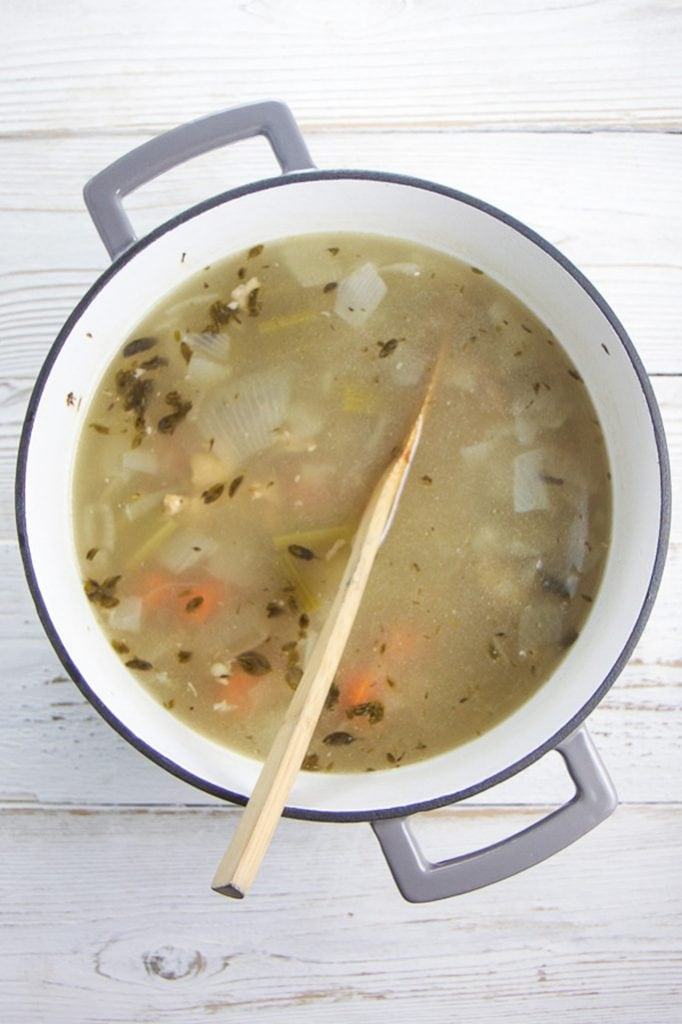 A white stockpot with grey rim on a wooden board filled with chicken bones, herbs and veggies and water and simmered.