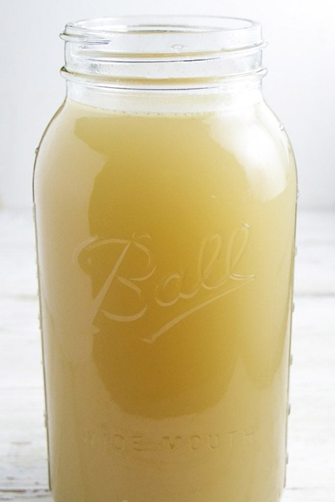 A clear ball jar shot from the side filled with a rich easy homemade chicken stock to be used in baby food purees