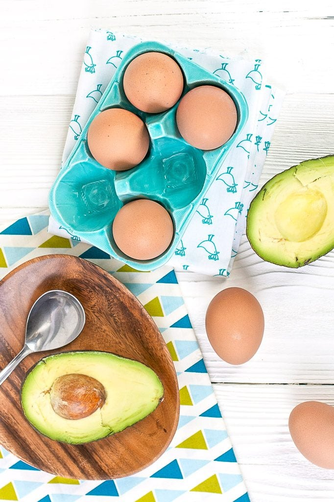 Brown eggs and cut in half avocados are scattered about a white wooden board with napkins in teal and green.