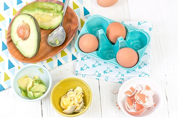 There is a wooden plate with a cut open avocado, a teal egg holder with 3 brown eggs and 3 bowls in front - 1 bowl is filled with avocado, 1 bowl is filled with hard boiled eggs and the other bowl is filled with egg shells.