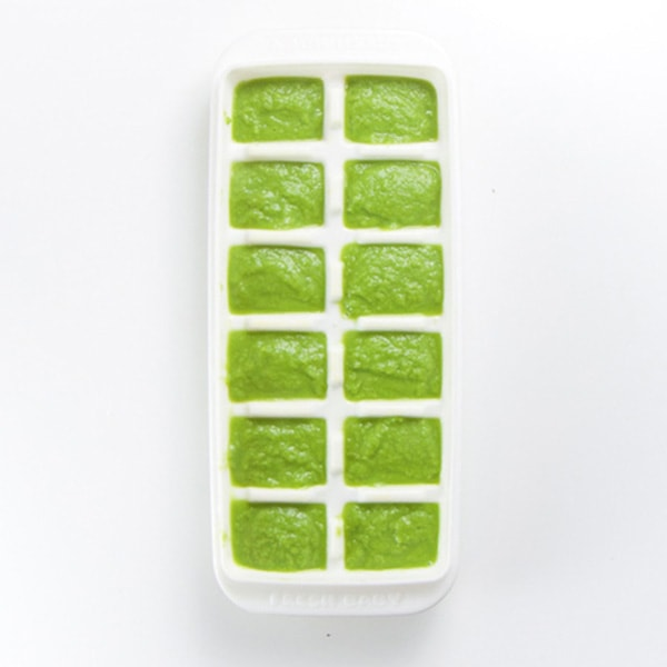 A white storage tray is filled with green bean baby food puree.