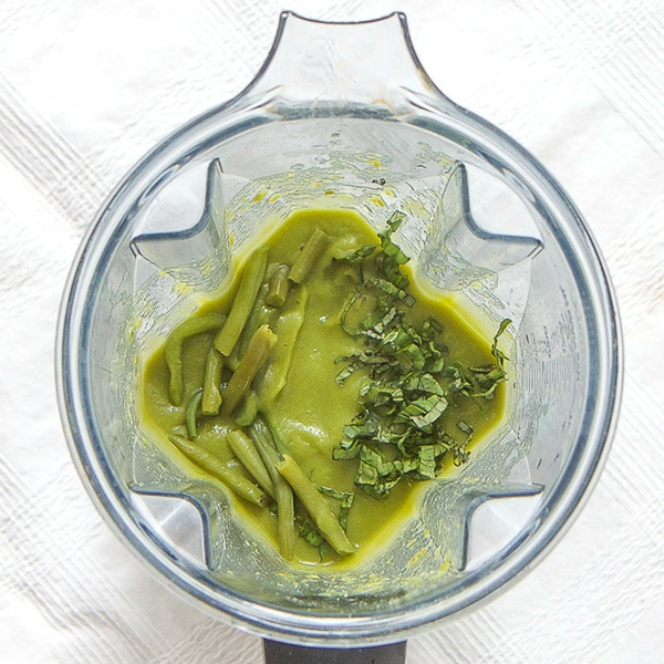 A clear blender is filled with a green bean puree with chunks of green beans and parsley on top