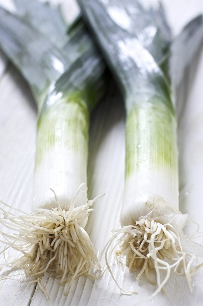 An unclose shot of 2 leeks sitting next to each other on top of a white wooden surface.
