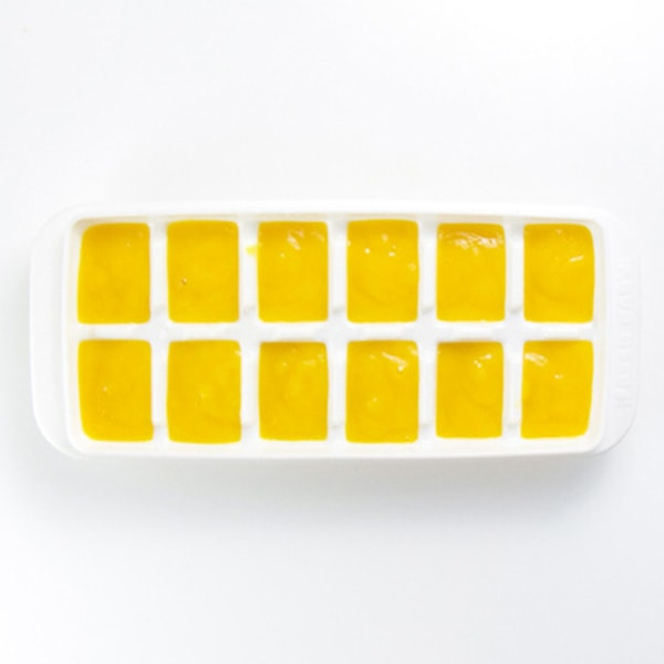 A white ice cube tray is filled with a healthy mango baby food puree