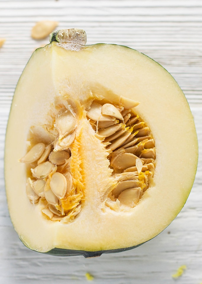 An up close of a cut open acorn squash with it's seeds still intact. The squash is sitting on a white wooden surface.
