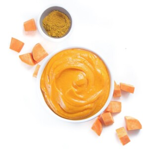 A bowl of sweet potato baby food puree with chunks of sweet potato and a bowl of curry powder next to it.
