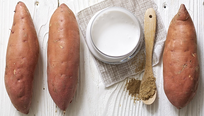 3 sweet potatoes sitting on a white wooden board with a glass jar of coconut milk and a wooden spoon full of coriander.