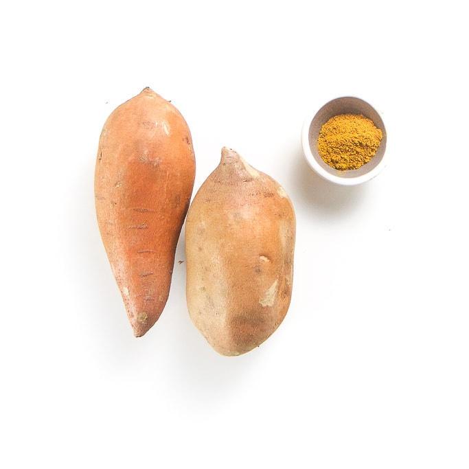 2 sweet potatoes nestled together with a small grey and white bowl filled with curry powder sitting next to them on a white background.