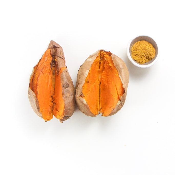 two cooked sweet potatoes sitting next to each other cut open down the middle. There is a small bowl filled with mild curry powder sitting next to the potatoes, all on a white background.