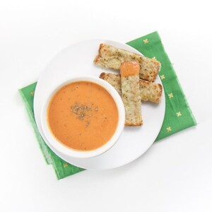 small white bowl filled with an easy creamy tomato soup is sitting on a white plate with 3 cheesy dippers next to the bowl. The bowl is on a green napkin sitting on a white surface.