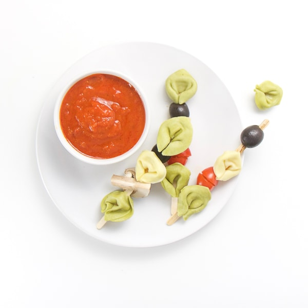 small white plate sitting on a white surface. On top of plate is a small white bowl filled with a dipping sauce and 3 wooden sticks filled with tortellini and veggies, a couple of tortellini and veggies are scattered on the table.