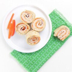 a small white plate sitting on a green napkin on top of a white surface. Place has 4 turkey and carrot rollups wit 3 slices of red peppers on the plate. On the napkin is one half eaten rollup.
