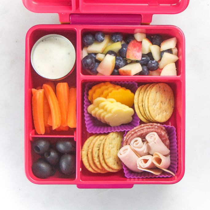 Pink school lunch box filled with healthy and easy school lunch ideas - cheese, crackers, fruit and carrots and ranch.