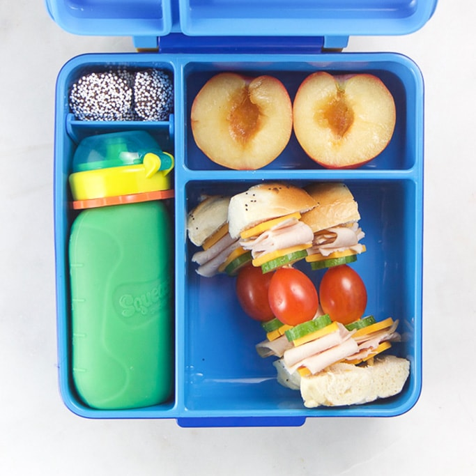 Blue school lunch box filled with healthy foods for kids.