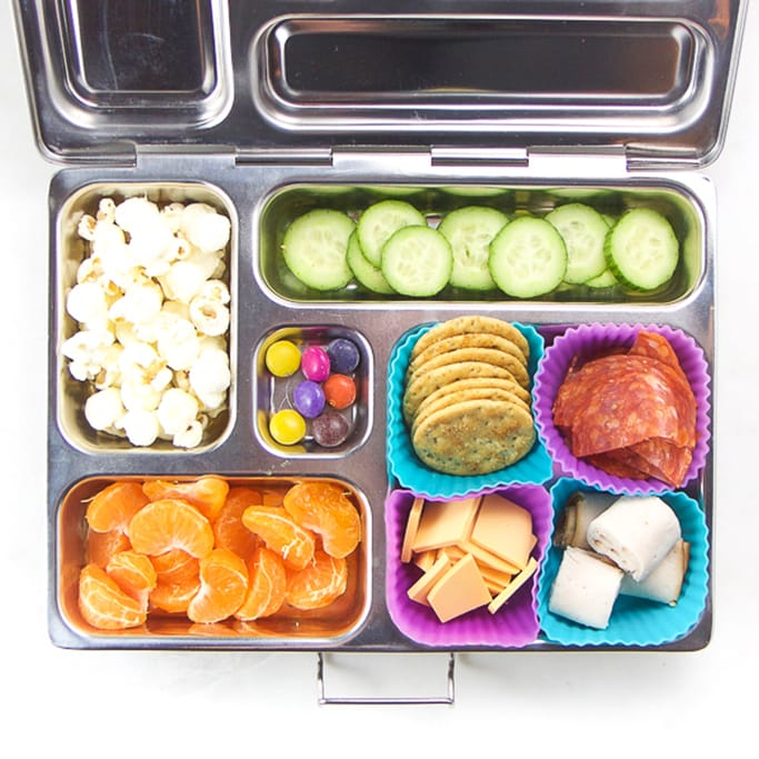silver planetbox filled with crackers, cheese, turkey, salami, cucumbers, popcorn and orange slices.