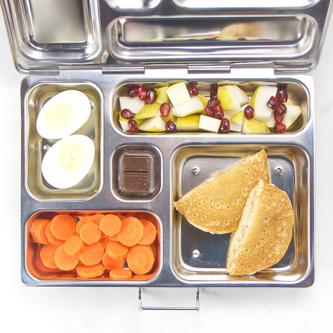school lunch box for kids filled with pancake and cream cheese sandwich, pear and pomegranate salad hard boiled egg, carrot coins.