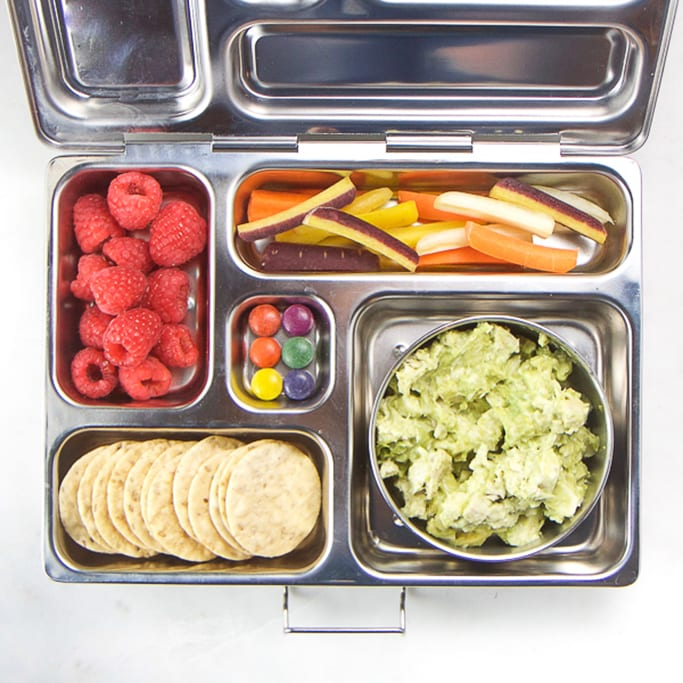 silver planet box filled with avocado chicken salad, carrots, raspberries, crackers and candy for a great allergy-free school lunch box for kids.