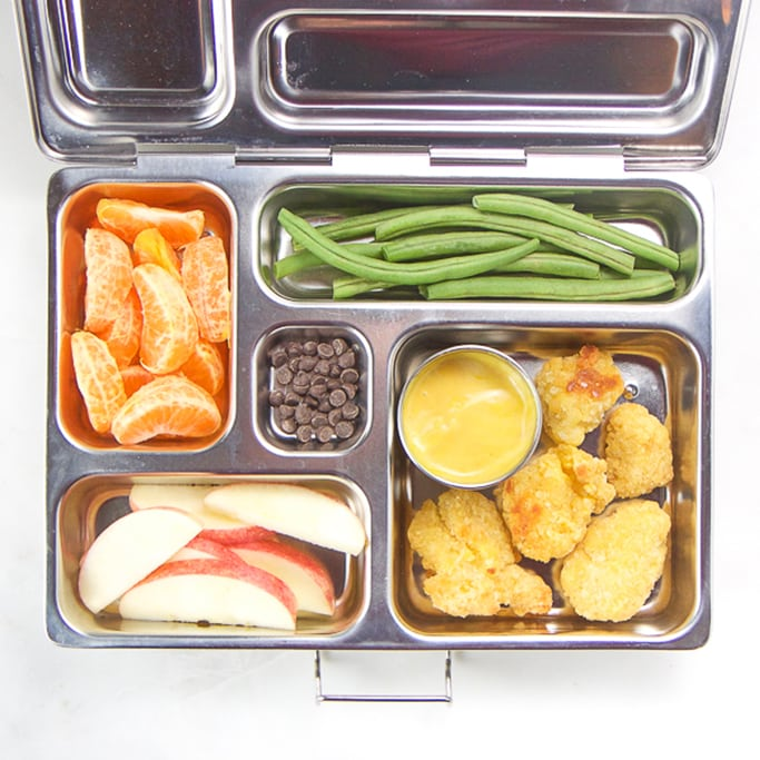 lunch box for kids filled with gluten free chicken nuggets, apple slices, green beans, oranges and chocolate chips