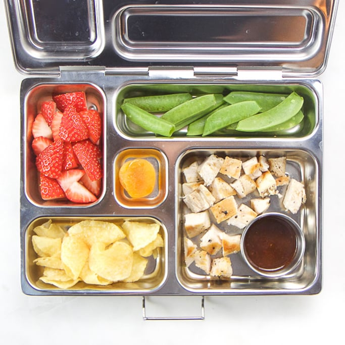 silver planetbox filled with grilled chicken and bbq sauce, chips, snap peas, strawberries and dried fruit.
