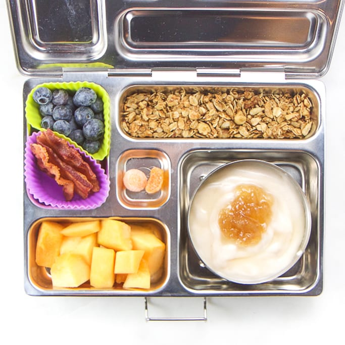 school lunch box filled with coconut yogurt, apples, granola, back, blueberries and gummies.