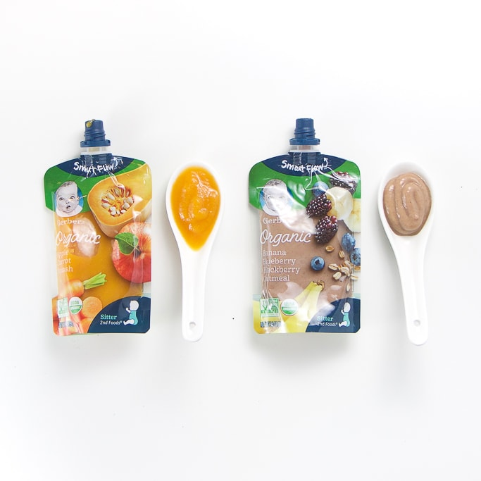 2 organic happy baby baby food pouches with spoons next the them with puree inside.