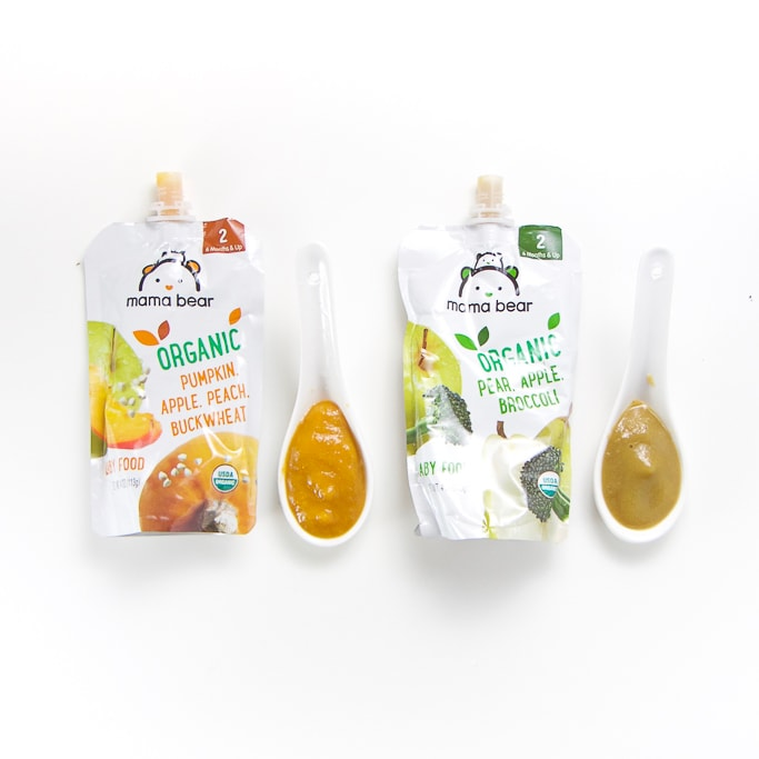 2 Mama Bear baby food pouches with spoons next the them with puree inside.