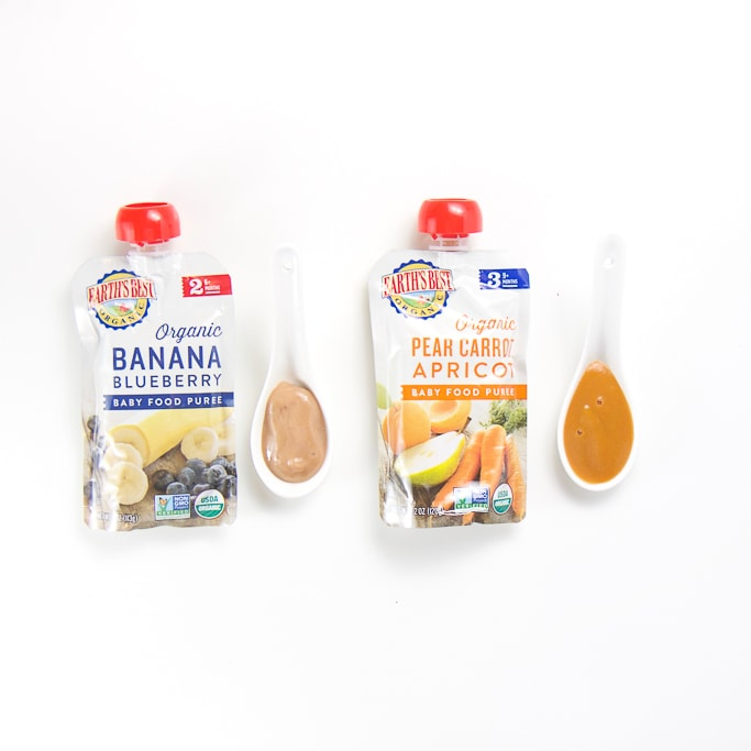 2 organic earths best baby food pouches with spoons next the them with puree inside.