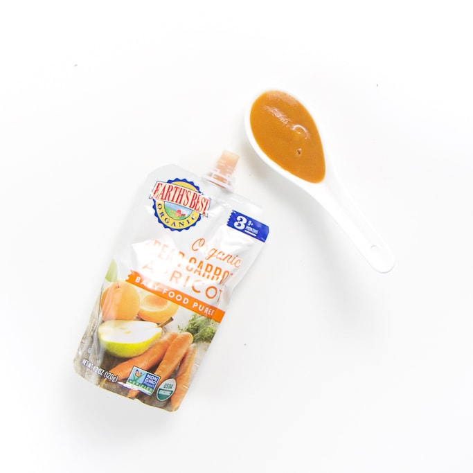 organic baby food brand pouch with a spoon filled with it's puree