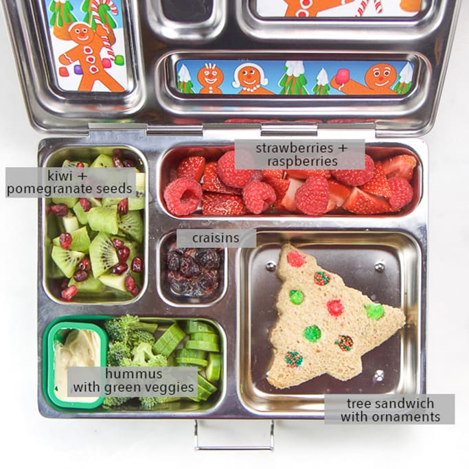 A silver planetbox lunch box filled with christmas tree sandwich and other holiday themed foods for kids.