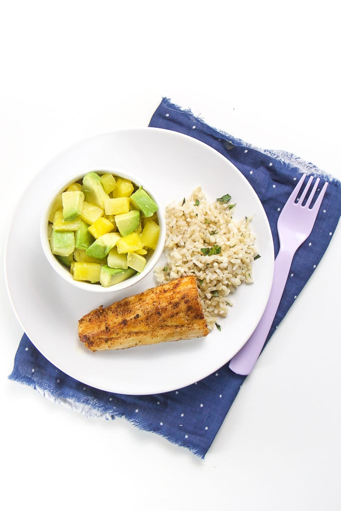 Round white place with crispy white fish, rice and pineapple and avocado salad.