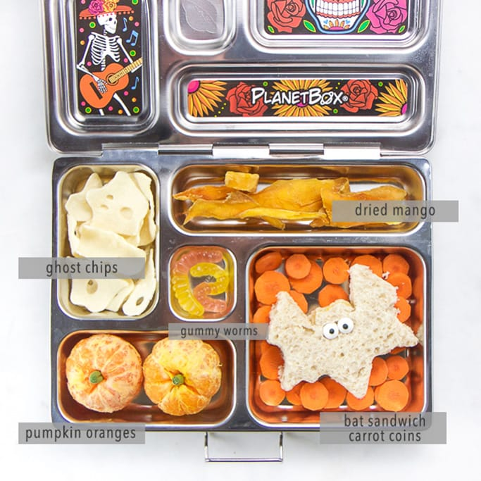 A silver school lunch box filled with halloween themed healthy foods for kids.