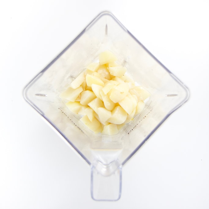 A clear blender filled with simmered pear chunks.