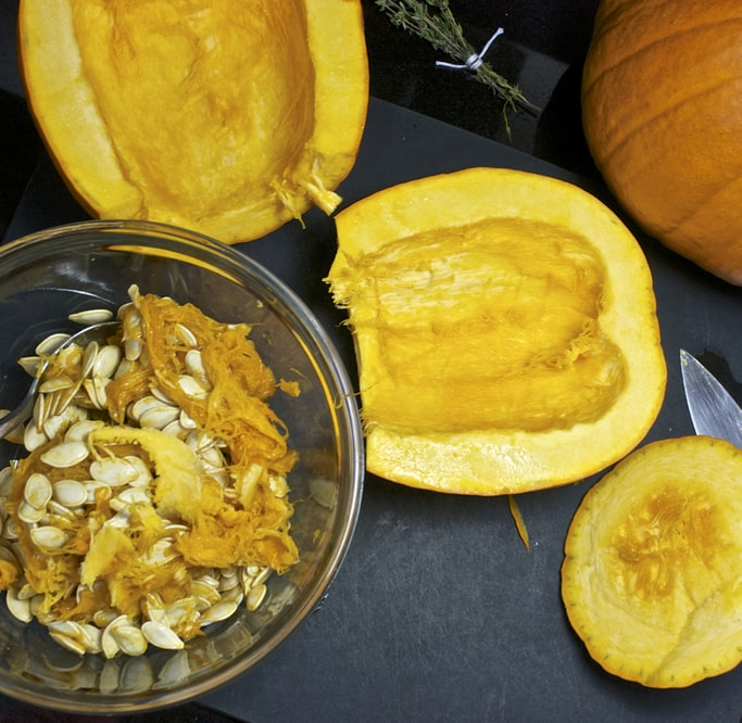 a bowl full of seeds and 2 halves of the pumpkin on either side of the bowl