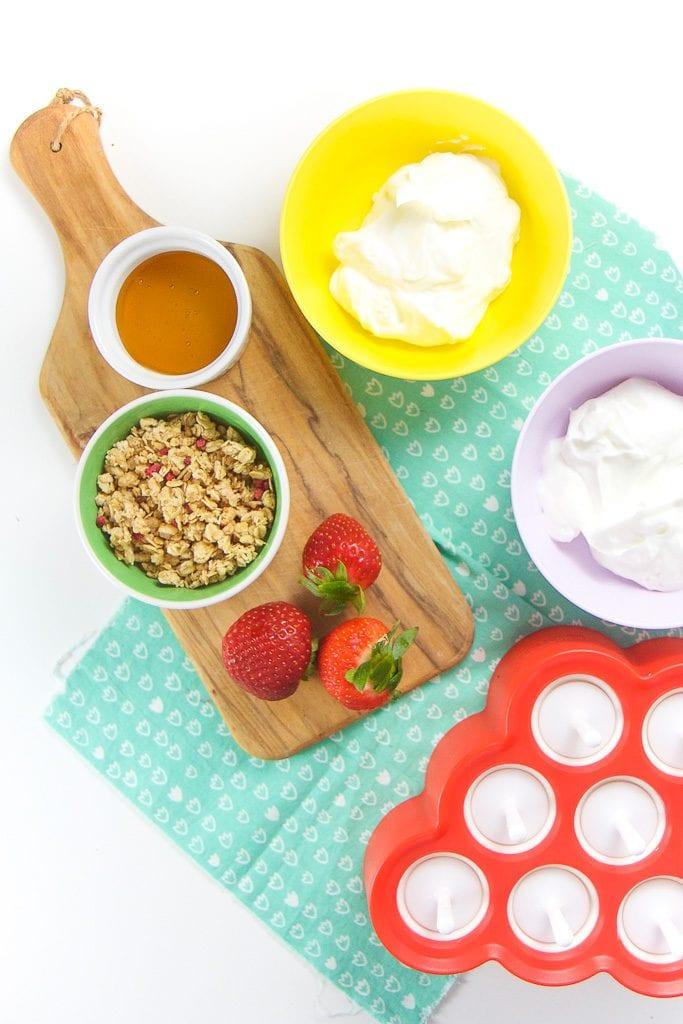 Everything you need to make healthy yogurt parfait popsicles for toddler + kids - yogurt, strawberries, granola honey.