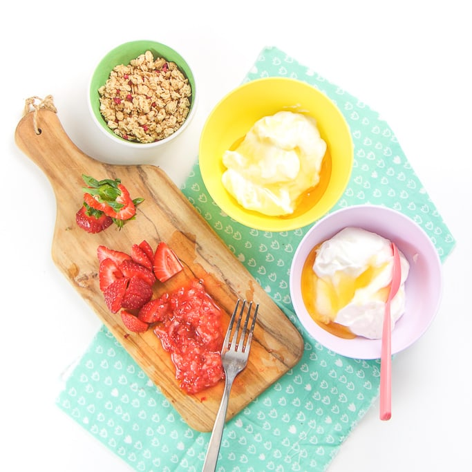 Bowls of yogurt, cutting board with smashed strawberries and granola - everything you need to make heathy yogurt parfaits for toddler and kids.