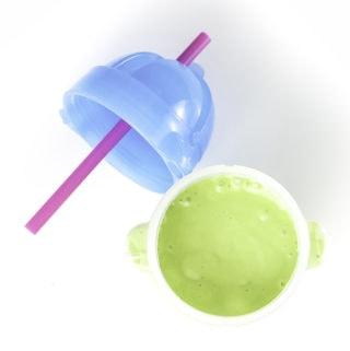Clear sippy cup filled with a green avocado smoothie for baby and toddler sitting on a white surface.