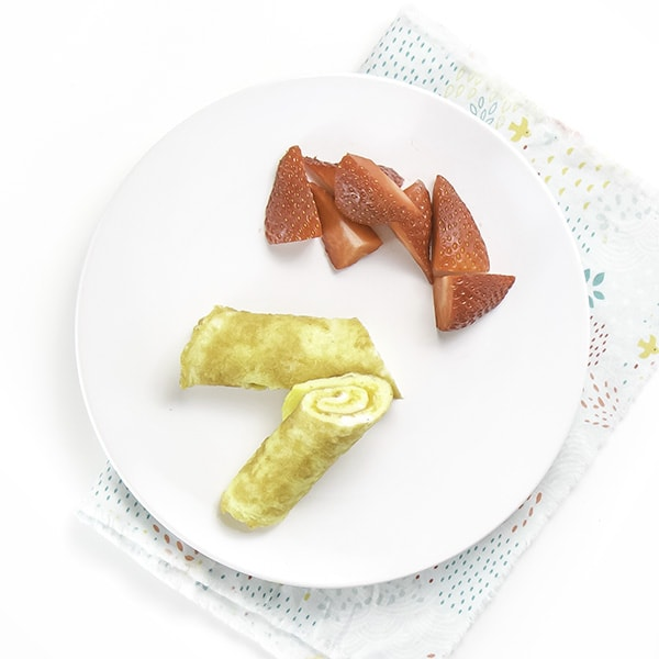 A round white plate with 2 easy-cheesy egg roll-ups on top with some chopped strawberries.