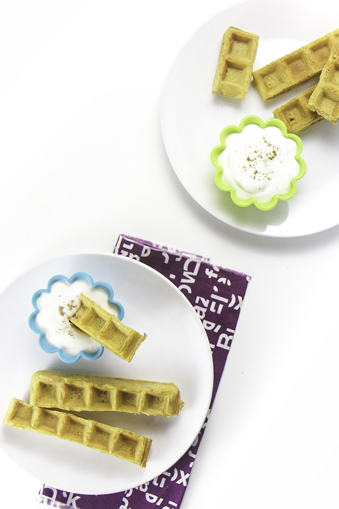 Overhead photo of 2 plates with pumpkin waffle dippers with cups filled with yogurt.